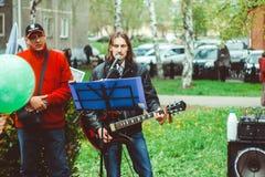 Ryssland Sibirien, Novokuznetsk - kan 9, 2017: musiker sjunger i gatan Arkivbilder