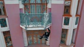 RYSSLAND ST PETERBURG-, 22 APRIL: flyg- sikt av målaren som in hänger på ett rep och målarfärger fasaden av en historisk byggnad lager videofilmer
