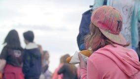 RYSSLAND ST PETERBURG-, 8 JUNI 2016: ung flicka som äter en hotdog Festival av färger Holi lager videofilmer