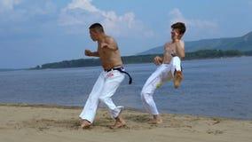 Ryssland Togliatty - Juli 11, 2018: Män utbildar capoeiraen på stranden - begrepp om folk, livsstil och sport arkivfilmer