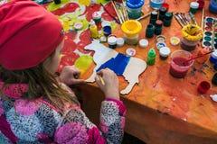 Ryssland Yaroslavl stad - Maj 4, 2019: Flickan drar på ett träbräde Barnet rymmer borsten Omkring finns på burk det målarfärger o royaltyfri illustrationer