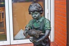 RYSSLAND ZELENOGRADSK - OKTOBER 11, 2014: Skulptur av en pojke med fågeln i den Zelenogradsk promenaden Royaltyfri Bild
