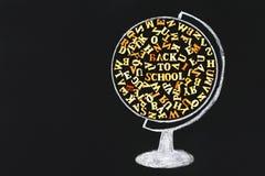 Rysująca kula ziemska zawiera drewnianych listy Angielski abecadło i inskrypcja Z powrotem szkoła na chalkboard Conce zdjęcie royalty free