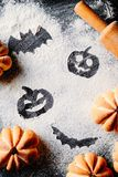 Rysujący Halloweenowej bani przewodzi dźwigarka nietoperz na pszenicznej mąki tle z tortami i lampion w formie bani, odgórny wido obrazy stock
