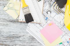 Rysunki, notatnik, żółty hełm, paintbrush i wyrwania, drewniany tło Obraz Royalty Free