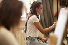 Rysunkowa lekcja w sztuki studiu Dziewczyny farba obrazuje obsiadanie przy sztalugami obrazy stock