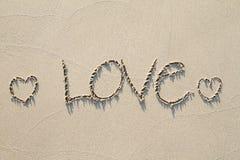Rysunkowa tekst miłość i dwa serca na piasek plaży z miękkim cieniem Zdjęcia Royalty Free