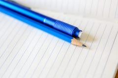 Rysunkowy ołówek i gumka nad białym notatnikiem Fotografia Stock