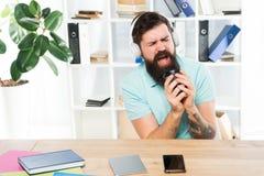 Rythme de la vie de bureau Jour régulier de bureau Les écouteurs barbus de type d'homme reposent le bureau écoutent musique chant images libres de droits
