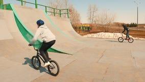 Ryttare f?r en bmx som utbildar deras expertis i skateparken p? en h?g hastighet Banhoppningen p? a upph?jer stock video
