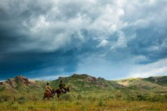 Ryttare på hästrygg Sommar betar i en intermontane dal royaltyfri bild
