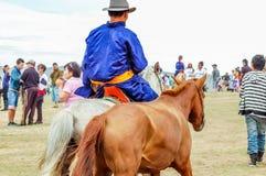 Ryttare som bär traditionell deel, Nadaam hästkapplöpning, Mongoliet Arkivbilder