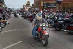 Ryttaren i den huvudsakliga gatan av staden av Sturgis, i South Dakota, USA, under den ettårig växtSturgis motorcykeln samlar arkivfoton