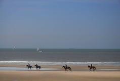 Ryttarna som galopperar längs stranden Arkivbild