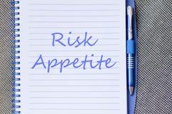Ryzyko apetyt pisze na notatniku Obrazy Royalty Free