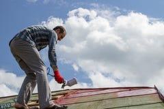 Ryzykowna praca na dachu, A mężczyzna pracuje na dachu bez wyposażenia Fotografia Royalty Free