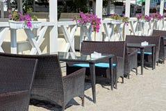 Rząd brązów stoły i karła w piasku blisko białego ogrodzenia z garnkami i kwiatami na lecie tarasujemy fotografia royalty free