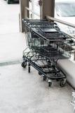 Rząd czarny wózek na zakupy z czarną rękojeścią wykładał up na cemencie zdjęcie royalty free