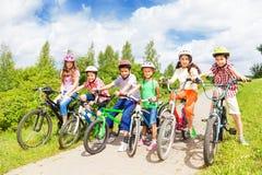 Rząd dzieciak różnorodność w hełmach i rowerach zdjęcia stock
