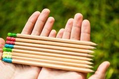 Rząd kolorów ołówki w rękach na zielonym krzaku Zdjęcia Royalty Free