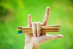Rząd kolorów ołówki w rękach na zielonym krzaku Obraz Royalty Free