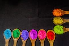Rząd kolorowy proszek barwi na drewnianej łyżce w czarnym tle zdjęcie stock