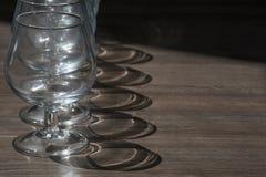 Rząd koniaków szkła z cieniami na drewnie Zdjęcia Royalty Free