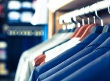 Rząd kurtki na wieszakach w mężczyzna sklepie odzieżowym zdjęcie stock