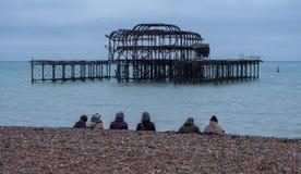 Rząd ludzie siedzi na żwirowatej plaży w Brighton UK na mroźnym popołudniu w Grudniu, przed ruinami Zachodni molo fotografia royalty free