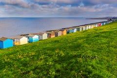 Rząd plażowe budy w wzdłuż wybrzeża Tankerton, Whitstable, Kent Zielonej trawy skłony są za groynes i budami fotografia royalty free