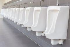 Rząd plenerowi pisuary na popielatej ścianie w mężczyzna jawnej toalecie zdjęcie royalty free