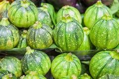 Rząd round zieleni courgettes na półce w rynku Fotografia Stock