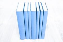 Stare błękitne książki na drewnianym biurku obraz stock