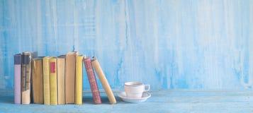 Rząd stare książki i filiżanka coffe na wieśniaka stołu panorma, r zdjęcie stock