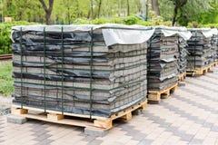 Rząd sterty szara bruk cegiełka na drewnianej bazie Betonowa kamienna brukowa flaga Odizolowywający na bielu zdjęcie stock
