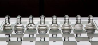 Rząd szklani szachowi pionkowie na desce z czarny i biały cieniem zdjęcie stock