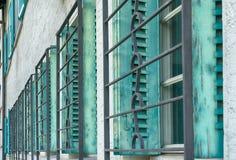 Rząd wiele zielone okno żaluzje, żelazo i uciera na mieści przód zdjęcie stock
