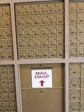 Rzędy małe metal skrzynki pocztowa wykładali przeciw ścianie z piszą list opadową szczelinę Fotografia Royalty Free