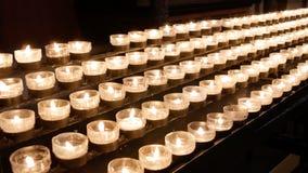Rzędy palenie zaświecali świeczki, tealights w Katolickim kościół chrześcijańskim/ zdjęcie stock