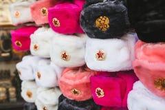 Rzędy rosyjscy zima kapelusze różni kolory z wojsko emblematami przy ulicznego rynku ikonową popularną pamiątką od zdjęcia stock