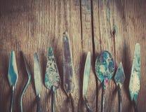 Rząd artysta palety knifes na starym drewnianym nieociosanym tle Fotografia Stock