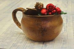 Rzadka gliniana herbaciana filiżanka z Bożenarodzeniową dekoracją na lekkim tle obrazy royalty free