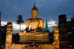 Rzeźba siedzący Buddha w nocy iluminaci przeciw tłu ponury niebo Sukhothai, Thailandd fotografia royalty free