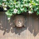 Rzeźbiąca drewniana Buddha głowa na drewnianej ścianie dekorował z kwitnienie rośliną bali Indonesia obraz stock