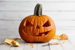 Rzeźbiąca Halloweenowa bania na białych deskach zdjęcie stock
