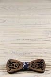 Rzeźbiący łęku krawat na drewnianym tle Obrazy Royalty Free