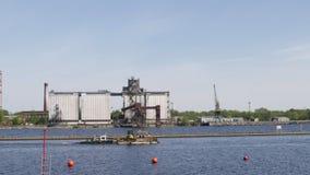 Rzeczny barki hoy iść wzdłuż rzecznego Daugava z escavator na pokładzie - Pogodnej pogody z portem w tle zdjęcie wideo