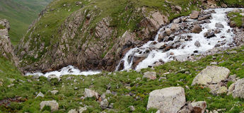 Rzeczny bieg między kamieniami w zielonej dolinie Obrazy Stock