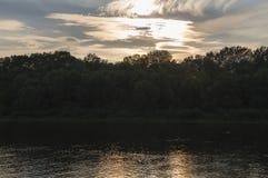 Rzeczny bieg przez z odbiciami w wodzie Wieczór zmierzch z menchiami i fiołkami barwi w niebie sylwetki Fotografia Stock