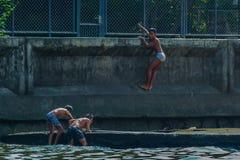 Rzeczny widok ch?opiec bawi? si? przy zatok? Dzieci skacze w wod? obraz stock
